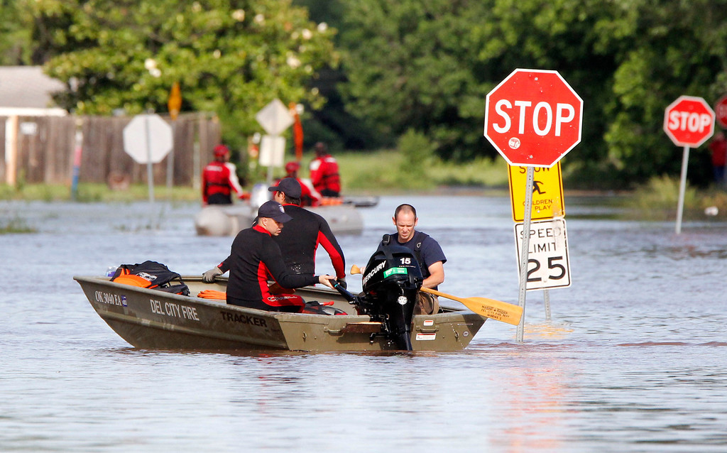 . Del City and Edmond Fire Dept. rescue crews use boats to rescue residents from a flooded mobile home park off of Air Depot Blvd. between NE 10th and NE 23rd St. in Midwest City, Okla, Saturday, June 1, 2013, after up to eight inches of rain fell during the previous 24 hours. (AP Photo/The Oklahoman, Paul Hellstern)