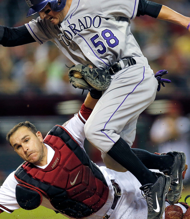 . Colorado Rockies\' Jordan Pacheco (58) is tagged out by Arizona Diamondbacks catcher Miguel Montero after trying to advance on a bad pitch during the fourth inning of a baseball game on Monday, April 28, 2014, in Phoenix. (AP Photo/Matt York)