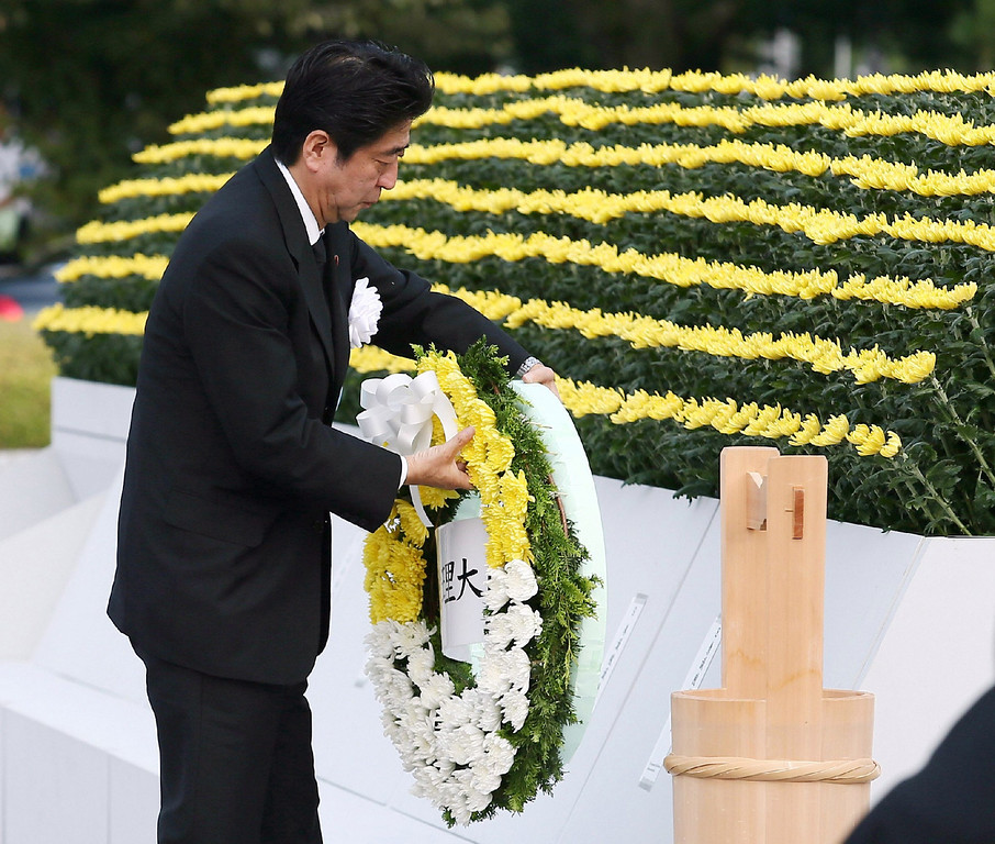. Japanese Prime Minister Shinzo Abe lays a flower wreath on an altar for A-bomb victims at the Peace Memorial Park in Hiroshima, western Japan on August 6, 2013 as ceremonies are held to mark the 68th anniversary of the bombing.    AFP PHOTO / JIJI PRESS  /AFP/Getty Images