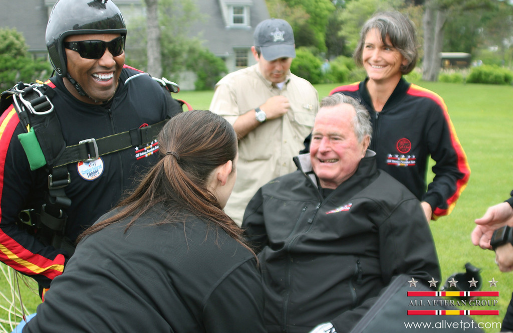 . In this photo provided by the All Veteran Parachute Team, former President George H.W. Bush is checked by a doctor with the All Veteran Parachute Team after his landing of a parachute jump on his 90th birthday in Kennebunkport, Maine, Thursday, June 12, 2014. (AP Photo/All Veteran Parachute Team, Kenneth Wasley)