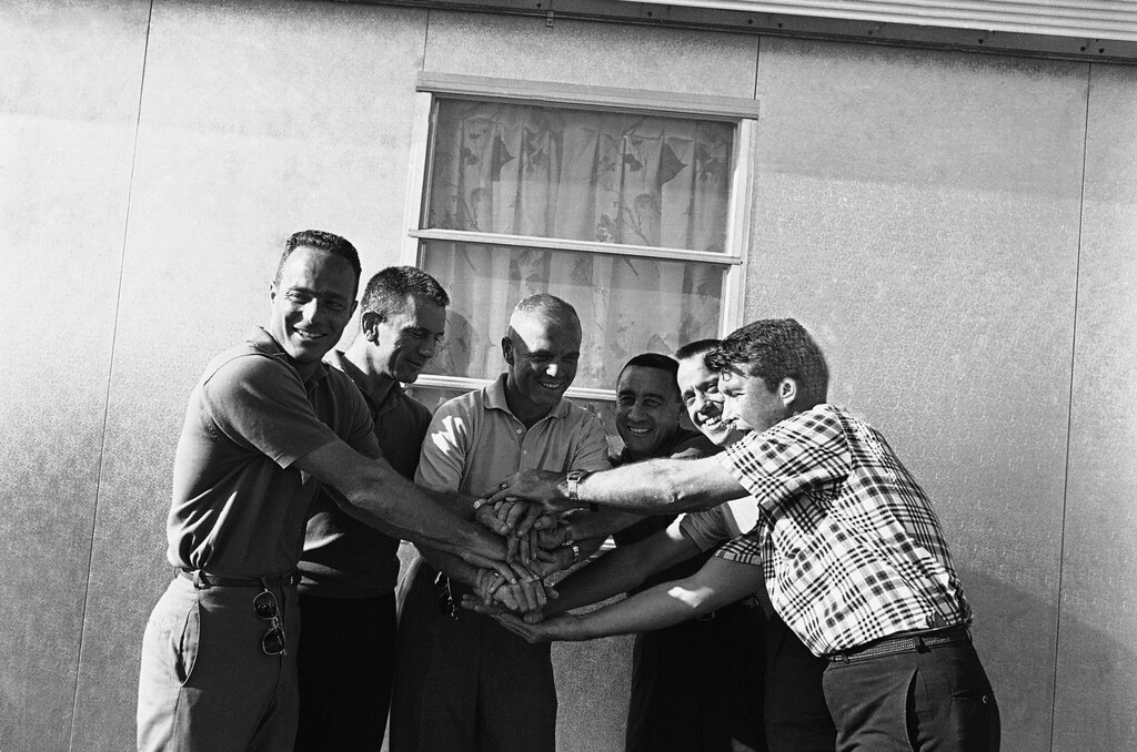 . John Glenn, center, is greeted by fellow astronauts following his orbital flight, Feb. 23, 1962,  Grand Turk Island, Turks and Caicos Islands. Left to right is: Scott Carpenter, Donald Slayton, Glenn, Virgil Grissom, Alan Shepard and Walter Schirra. The seventh member of the astronaut team, Leroy Cooper, was not available. (AP Photo/Pool)