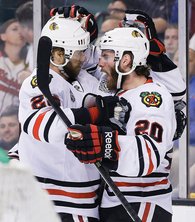 . Chicago Blackhawks left wing Brandon Saad (20) congratulates Blackhawks center Michal Handzus, left, of Slovakia, during the first period in Game 4 of the NHL hockey Stanley Cup Finals, Wednesday, June 19, 2013, in Boston. (AP Photo/Elise Amendola)
