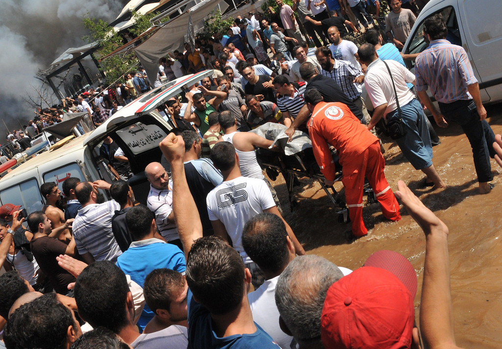 . Rescuers evacuate the body of a victim of a powerful explosion near al-taqwa mosque in the northern Lebanese city of Tripoli on August 23, 2013.   AFP PHOTO  IBRAHIM  CHALHOUB/AFP/Getty Images