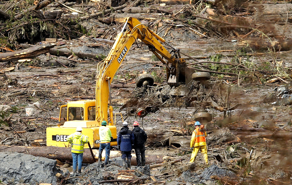 . Workers look on as a vehicle is moved by a piece of heavy equipment as search work continues Thursday, March 27, 2014, in the mud and debris from the massive mudslide that struck Saturday near Darrington, Wash. (AP Photo/Ted S. Warren, Pool)