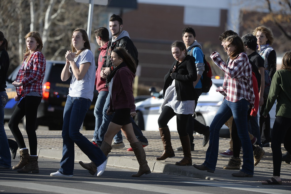. CENTENNIAL, CO. - DECEMBER 13: Students are escorted out of Arapahoe High School in Centennial, CO December 13, 2013. A student who carried a shotgun into Arapahoe High School and asked where to find a specific teacher opened fire on Friday, wounding two fellow students before apparently killing himself, Arapahoe County Sheriff Grayson Robinson said. (Photo By Craig F. Walker / The Denver Post)
