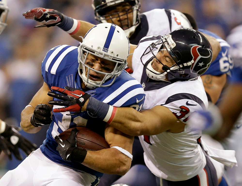 . Indianapolis Colts running back Donald Brown, left, is tackled by Houston Texans free safety Shiloh Keo during the first half of an NFL football game in Indianapolis, Sunday, Dec. 15, 2013. (AP Photo/Michael Conroy)
