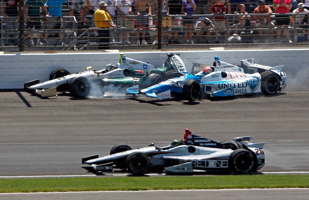 . James Hinchcliffe (27) and Ed Carpenter crash in the first turn during the 98th running of the Indianapolis 500 IndyCar auto race at the Indianapolis Motor Speedway in Indianapolis, Sunday, May 25, 2014. Kurt Busch, bottom, avoids the crash. (AP Photo/Kirk DeBrunner)