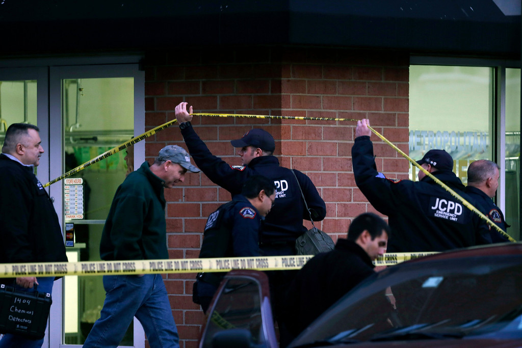 . Police and officials gather at a residence at the intersection of 13th and Grand streets in Hoboken, N.J. on Friday, Dec. 14, 2012. Local police and the FBI converged on the residence this afternoon after a connection was reported with the shootings at the Sandy Hook Elementary School in Newtown, Conn. (AP Photo/Mel Evans)