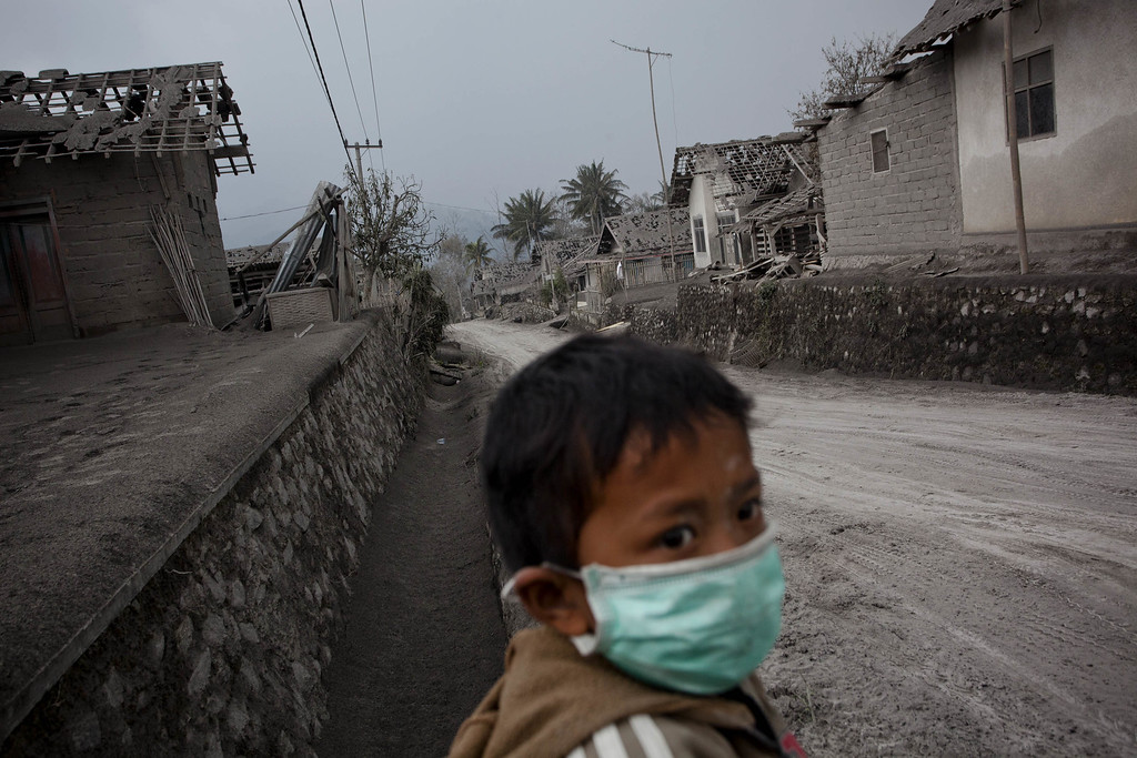 . A boy wears a mask in an area covered by ash after the eruptions of Mount Kelud at Pandansari village on February 16, 2014 in Malang Regency, Indonesia. More than 100,000 people were evacuated from villages on the Indonesian island of Java yesterday, after Mount Kelud erupted, spewing ash and lava 17km into the sky. (Photo by Ulet Ifansasti/Getty Images)