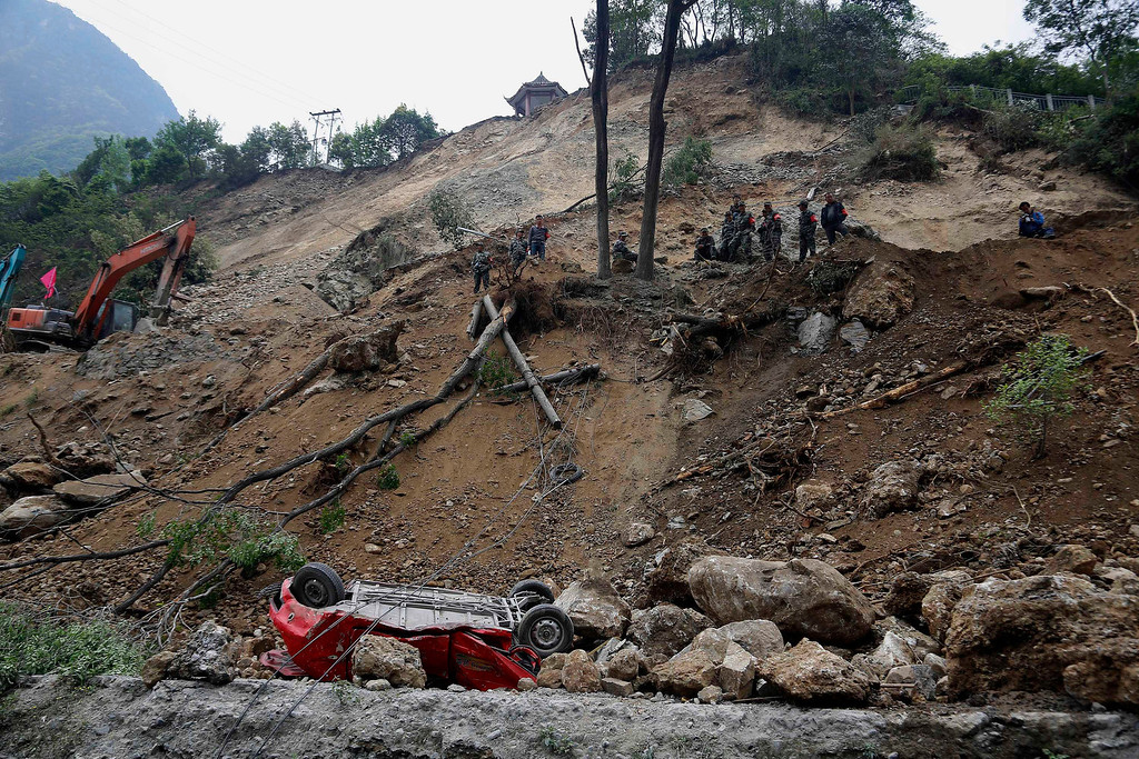 . Chinese rescue workers survey a road destroyed by an earthquake in Baoxing county in southwestern China\'s Sichuan province, Monday, April 22, 2013.  (AP Photo)