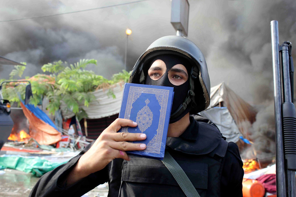 . A member of the Egyptian security forces holds up a copy of the Quran they clear the smaller of the two sit-ins by supporters of ousted Islamist President Mohammed Morsi, near the Cairo University campus in Giza, Cairo, Egypt, Wednesday, Aug. 14, 2013.  (AP Photo/Imad Abdul Rahman)