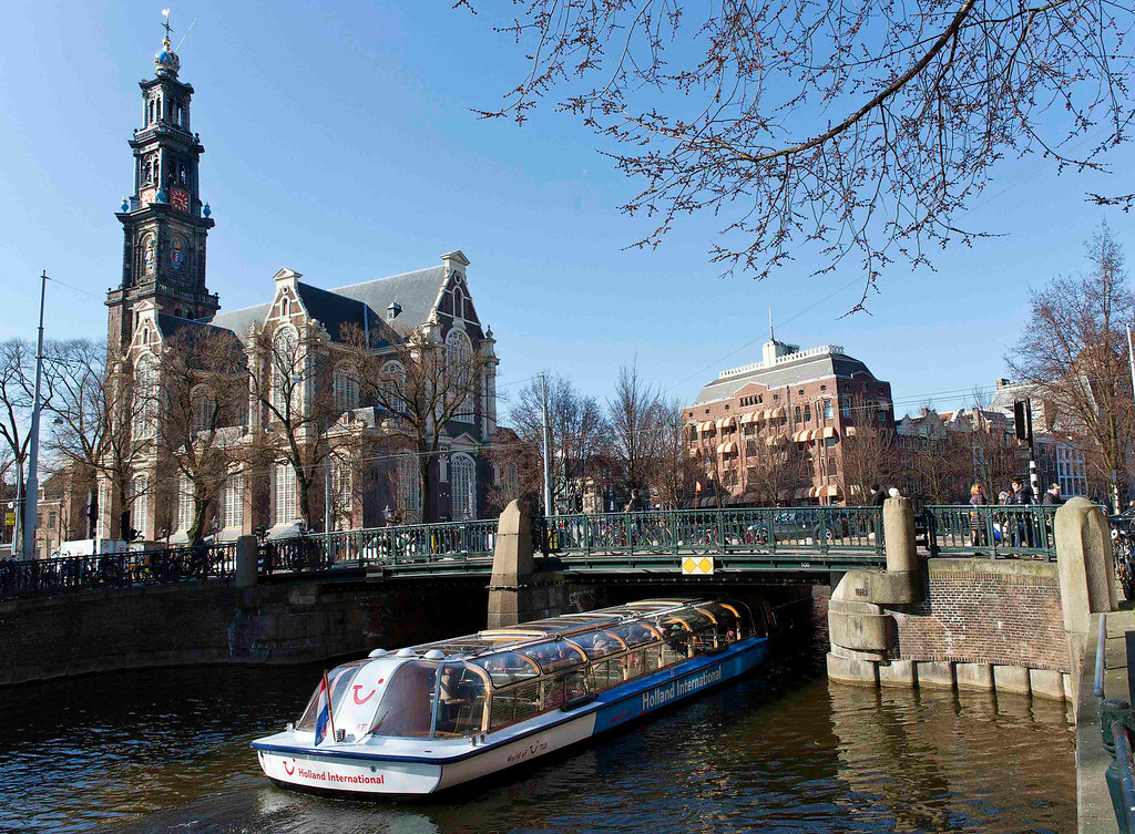 . A tourist boat passes under a bridge next to the Westerkerk church in Amsterdam April 2, 2013. The Royal celebrations in the Netherlands this week put the country and the capital Amsterdam on front pages and television screens around the world with an orange splash. There\'s plenty to see and do in 48 hours in this compact city, where the world-famous Rijksmuseum only recently reopened after an extensive renovation. Picture taken April 2, 2013. REUTERS/Michael Kooren