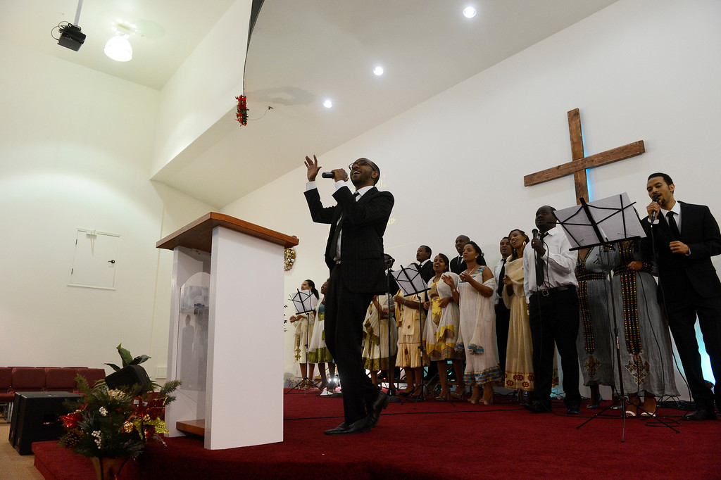 . AURORA, CO. - JANUARY 11:  Addis Kidan Evangelical Church worship team member, Etana Disasa, left, leads his choir during their church dedication, Saturday morning, January 10, 2014. (Photo By Andy Cross / The Denver Post)