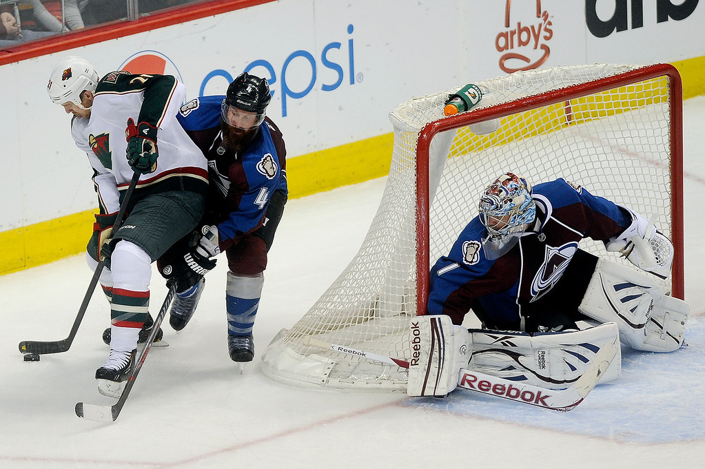 . Greg Zanon (4) of the Colorado Avalanche forces Kyle Brodziak (21) of the Minnesota Wild off the puck during the second period, Saturday, April 27, 2012 at Pepsi Center. Seth A. McConnell, The Denver Post