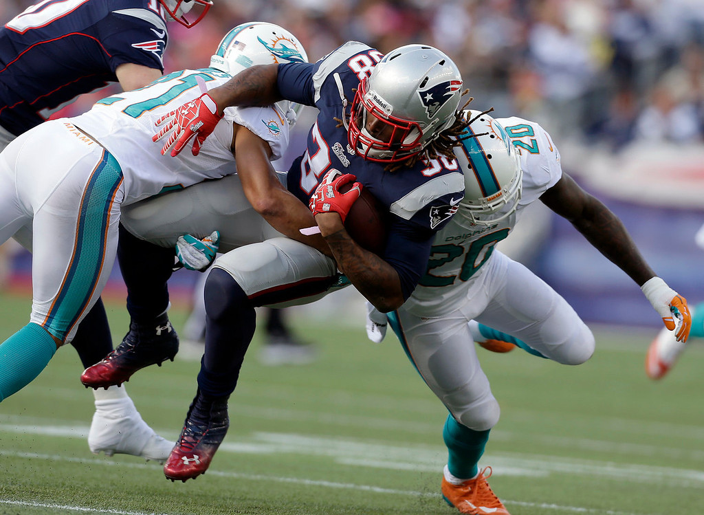 . Miami Dolphins defensive backs Brent Grimes, left, and Reshad Jones (20) tackle New England Patriots running back Brandon Bolden (38) in the first half of an NFL football game on Sunday, Oct. 27, 2013, in Foxborough, Mass. (AP Photo/Steven Senne)