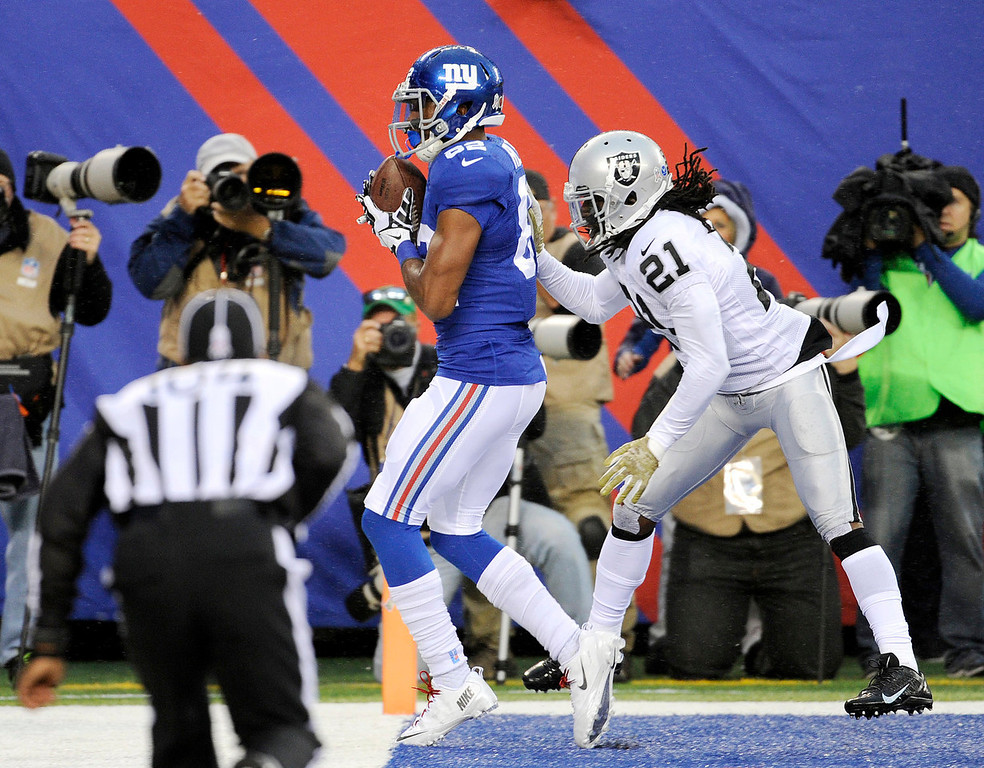 . New York Giants wide receiver Rueben Randle keeps his feet in bounds as he catches a touchdown pass as Oakland Raiders cornerback Mike Jenkins (21) defends on the play during the first half of an NFL football game, Sunday, Nov. 10, 2013, in East Rutherford, N.J. (AP Photo/Bill Kostroun)