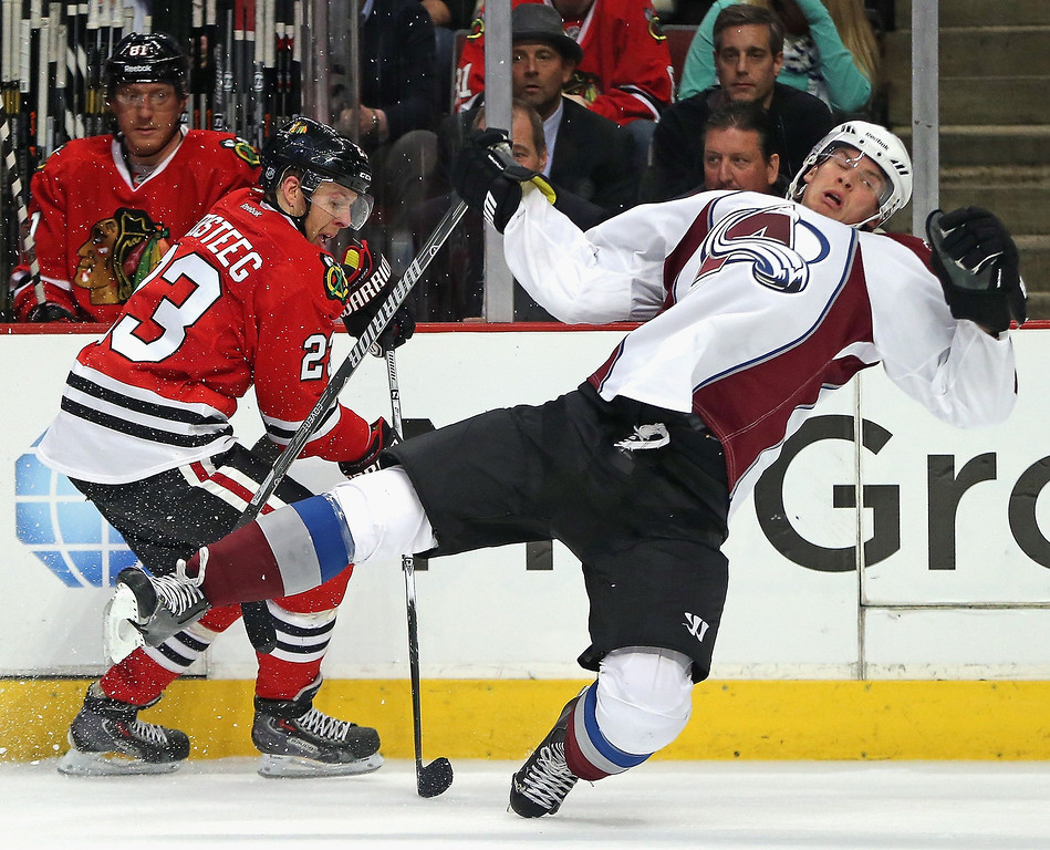 . Nick Holden #2 of the Colorado Avalanche falls to the ice trying to stop Kris Versteeg #23 of the Chicago Blackhawks at the United Center on January 14, 2014  in Chicago, Illinois. (Photo by Jonathan Daniel/Getty Images)