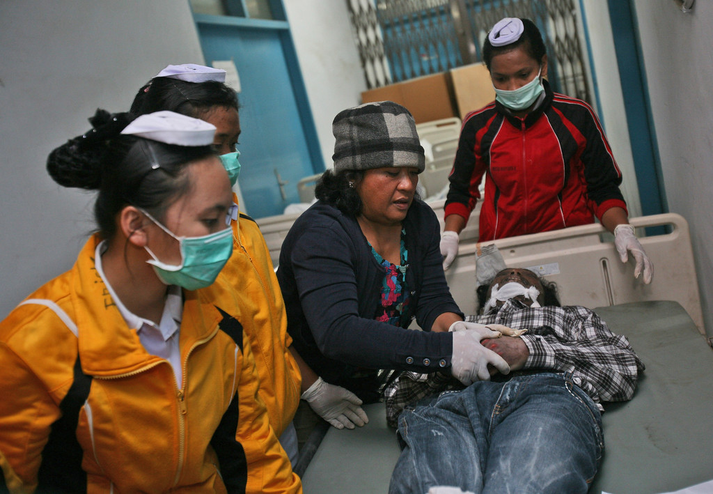 . Nurses dress a victim of the eruption of Mount Sinabung for burial at a hospital in Kabanjahe, North Sumatra, Indonesia, Saturday, Feb. 1, 2014.  (AP Photo/Binsar Bakkara)
