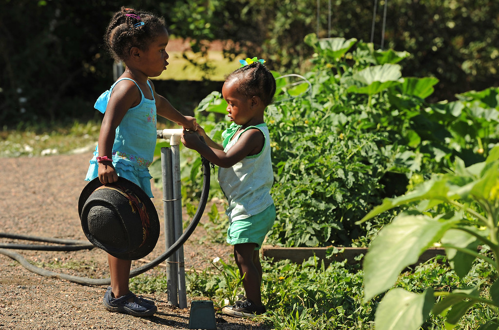 . DENVER, CO - JULY 3:   Selasia Leadon Vita, 3, left and her sister Libya, 21 months, play in the water as their parents DJ Cavem Moetivation (a.k.a. Ietef Vita) and his wife Neambe Vita, not shown, spend time tending their gardens at 33rd and Elm streets in Denver, CO on July 3, 2013.   The couple are proud and longtime Five Points residents. They\'re artists, community activists, musicians, teachers and more.  They espouse the idea of being vegan or vegetarian and promote eating healthfully and organically. The Couple is photographed in their home in Five Points on June 11, 2013.  (Photo by Helen H. Richardson/The Denver Post)