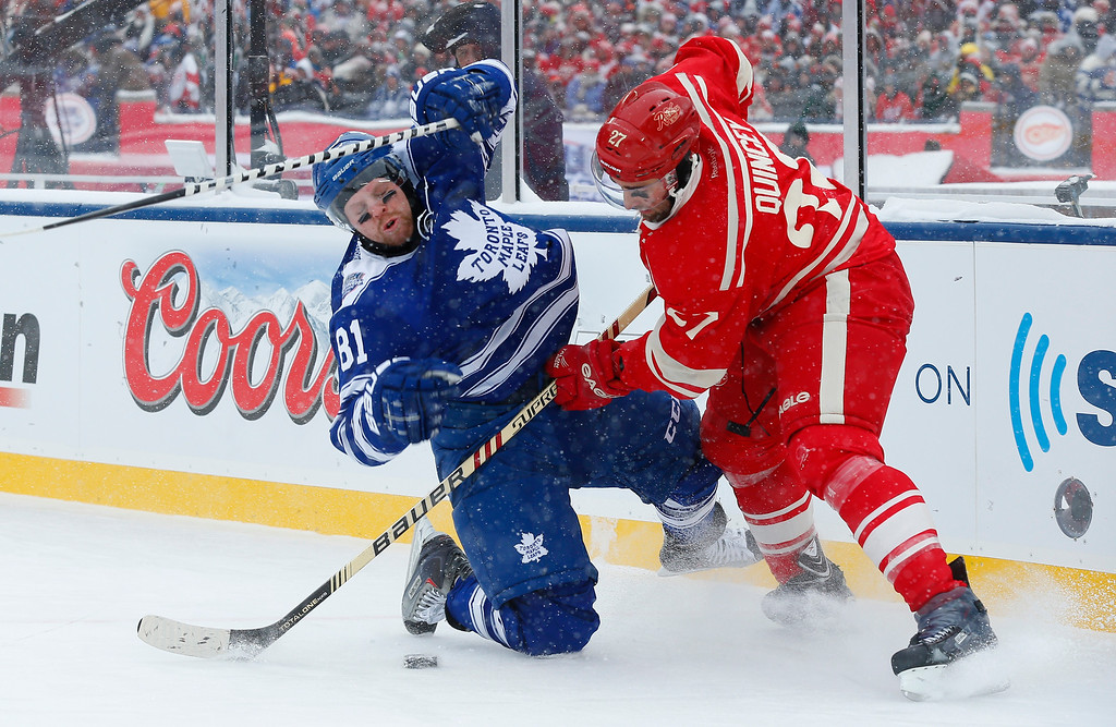 . Detroit Red Wings defenseman Kyle Quincey (27) checks Toronto Maple Leafs right wing Phil Kessel (81) during the first period of the Winter Classic outdoor NHL hockey game at Michigan Stadium in Ann Arbor, Mich., Wednesday, Jan. 1, 2014. (AP Photo/Paul Sancya)