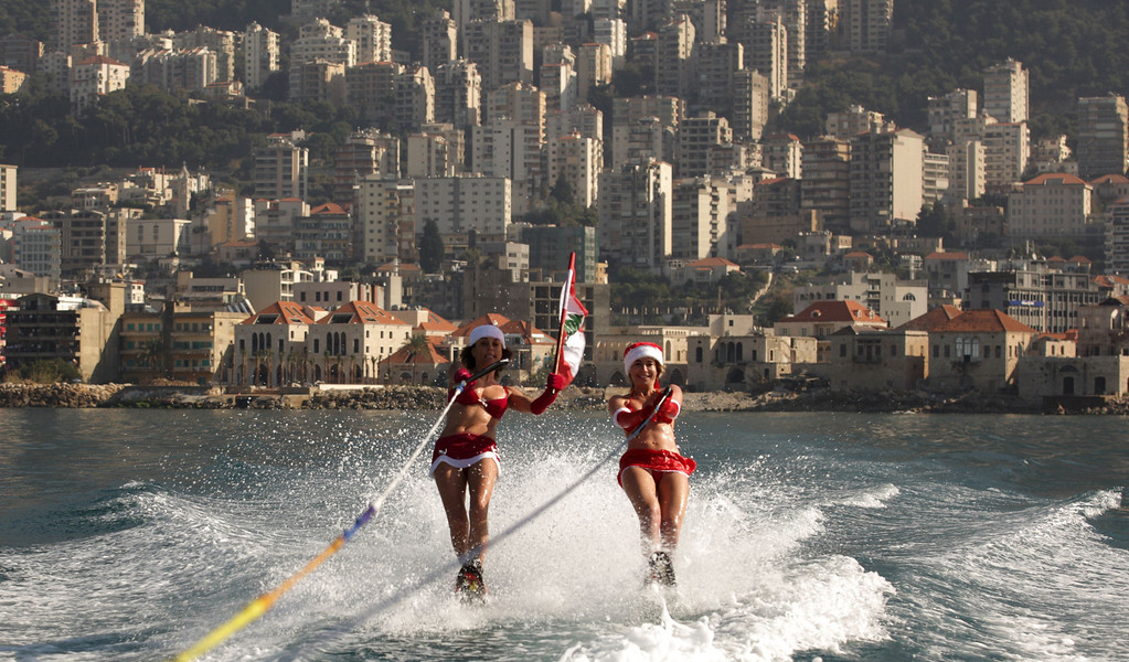 . Two Lebanese women wearing Santa Claus outfits and waving their national flag water ski during a show in the bay of Jounieh, 20 kms North of Beirut, on December 24, 2013.   PATRICK BAZ/AFP/Getty Images