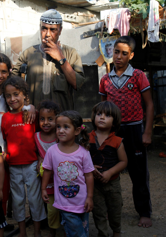 . In this Thursday, Sept. 12, 2013 photo, Salih Alwadiya, 61, center left, poses with some of his grandchildren in the yard of their family house in Gaza City, Thursday, Sept. 12, 2013. Alwadiya has three wives, 14 sons and 6 daughters. Most of the boys, married with children, are among the 38 people living in bad conditions in small rooms in the makeshift house. (AP Photo/Adel Hana)