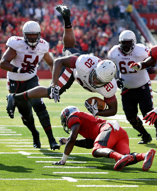 . Temple running back Kenneth Harper (20) dives for yardage over Rutgers defensive back Tejay Johnson (9) during the first half of an NCAA college football game in Piscataway, N.J., Saturday, Nov. 2, 2013. (AP Photo/Mel Evans)