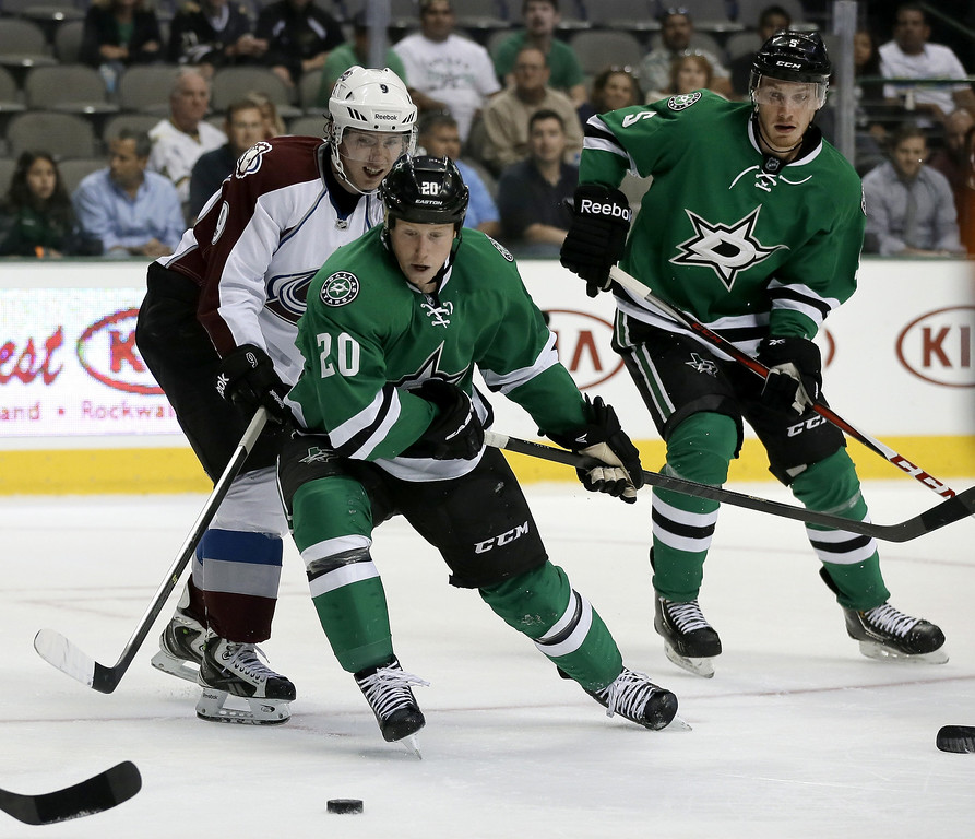 . Dallas Stars center Cody Eakin (20) and Colorado Avalanche center Matt Duchene (9) compete for a loose puck as Stars defenseman Jamie Oleksiak (5) watches in the second period of a preseason NHL hockey game on Thursday, Sept. 26, 2013, in Dallas. (AP Photo/Tony Gutierrez)
