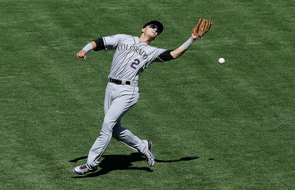 . Colorado Rockies shortstop Troy Tulowitzki cannot catch a fly ball hit by San Francisco Giants\' Brandon Crawford during the sixth inning of a baseball game in San Francisco, Wednesday, April 10, 2013. Brandon Belt scored, Andres Torres was out at second, and Crawford was safe at first. (AP Photo/Jeff Chiu)