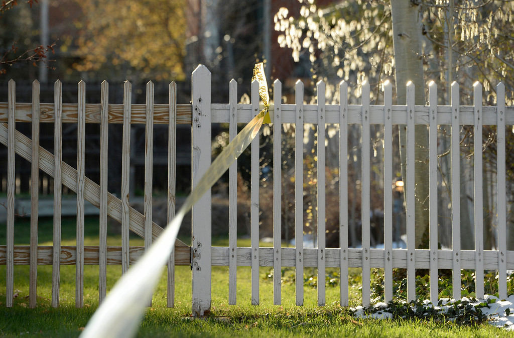 . Police tape is tied to a white picket fence near a home where Denver police are investigating a homicide at a home in the 2100 block of South Saint Paul Street in Denver, Tuesday, April 15, 2014.  (Photo by RJ Sangosti/The Denver Post)