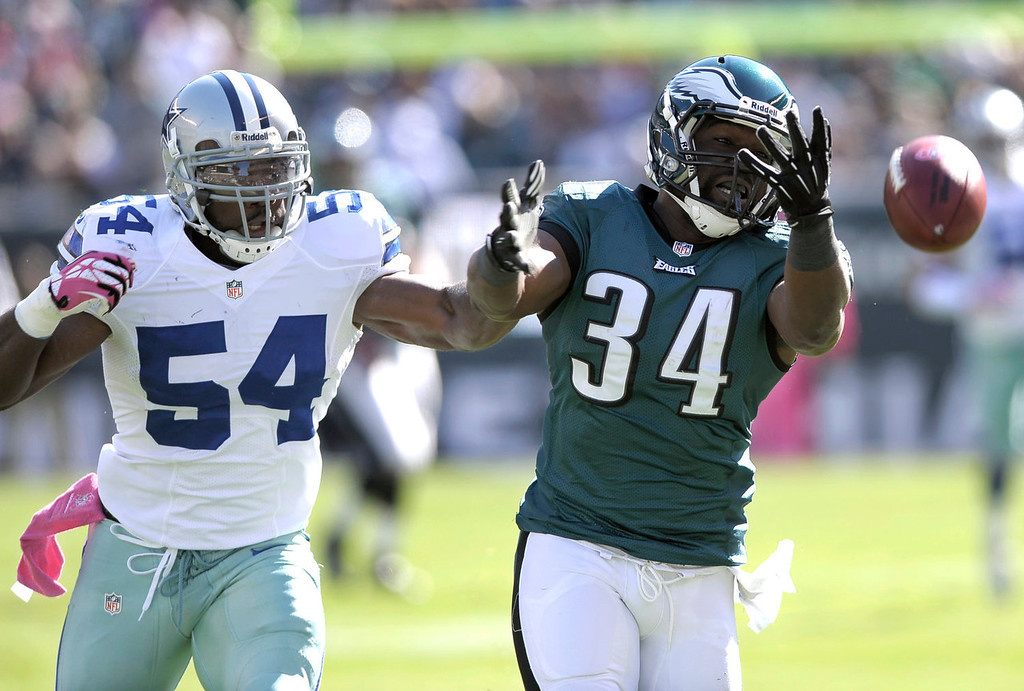 . Philadelphia Eagles running back Bryce Brown (34) is unable to catch a pass from quarterback Nick Foles as Dallas Cowboys outside linebacker Bruce Carter (54) defends on the play during the first half of an NFL football game, Sunday, Oct. 20, 2013, in Philadelphia. (AP Photo/Michael Perez)