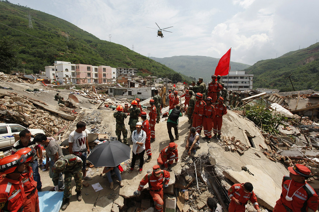. Rescuers stand over the debris of collapsed houses following an earthquake in Longtoushan township of Ludian county in Zhaotong, southwest China\'s Yunnan province, on August 5, 2014. AFP PHOTOSTR/AFP/Getty Images
