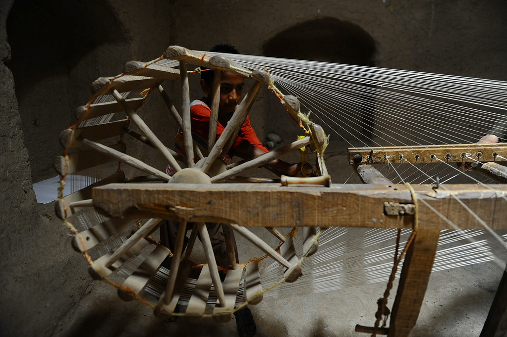 . In this picture taken on June 1, 2014, an Afghan child dries silk threads in a traditional factory in Zandajan district of Herat province. AFP PHOTO/Aref Karimi/AFP/Getty Images