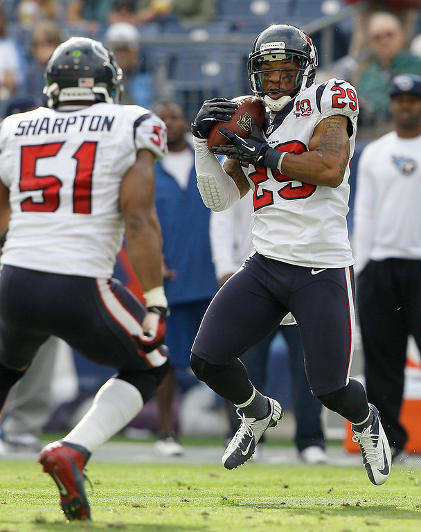 . Houston Texans safety Glover Quin (29) intercepts a pass thrown by Tennessee Titans quarterback Jake Locker, not shown, in the second quarter of an NFL football game on Sunday, Dec. 2, 2012, in Nashville, Tenn. At left is Texans inside linebacker Darryl Sharpton (51). (AP Photo/Wade Payne)