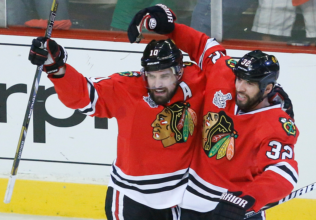 . Chicago Blackhawks center Patrick Sharp (10) celebrates with Chicago Blackhawks defenseman Michal Rozsival (32) after scoring against the Boston Bruins in the first period during Game 2 of the NHL hockey Stanley Cup Finals, Saturday, June 15, 2013, in Chicago. (AP Photo/Charles Rex Arbogast)