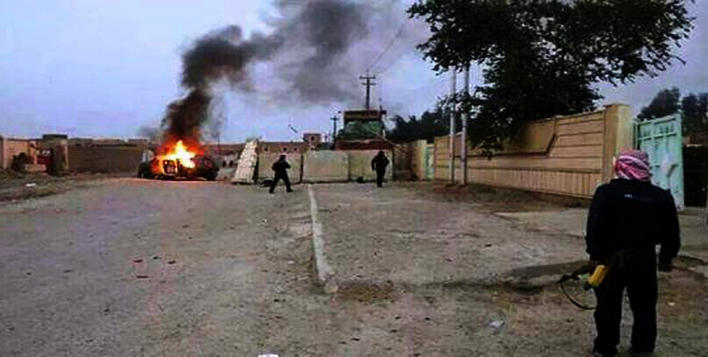 . A picture taken with a mobile phone shows an armed man watching as a vehicle, reportedly belonging to Iraqi security forces, is seen in flames on June 10, 2014 in Mosul, some 370 kms north from the Iraqi capital Baghdad. Some 500,000 Iraqis have fled their homes in Iraq\'s second city Mosul after Jihadist militants took control, fearing increased violence, the International Organization for Migration said. STR/AFP/Getty Images