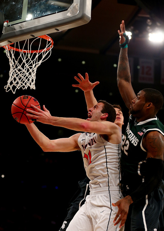 . Evan Nolte #11 of the Virginia Cavaliers goes to the basket against Branden Dawson #22 of the Michigan State Spartans during the regional semifinal of the 2014 NCAA Men\'s Basketball Tournament at Madison Square Garden on March 28, 2014 in New York City.  (Photo by Elsa/Getty Images)