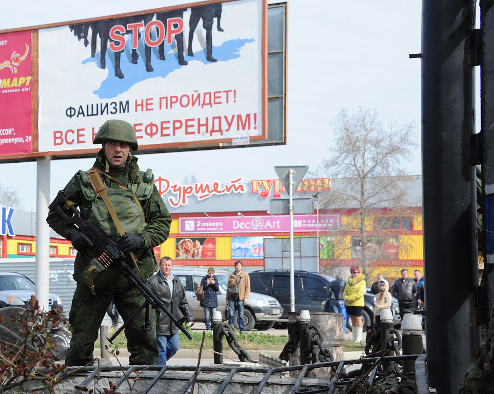 ". A Russian soldier patrols in front of a placard reading ""Fascism will not pass! All to the referendum!\"" near the Ukrainian navy headquarters in the Crimean city of Sevastopol on March 19, 2014.  Pro-Russian forces captured Ukraine\'s naval commander after seizing his headquarters in Crimea on Wednesday as Moscow\'s grip tightened on the peninsula despite Western warnings its \""annexation\"" would not go unpunished. FP PHOTO/  VIKTOR DRACHEV/AFP/Getty Images"