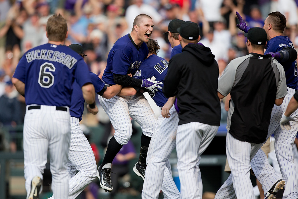 . DENVER, CO - JUNE 7:  Brandon Barnes #1 of the Colorado Rockies is mobbed by teammates after his game winning RBI triple in the 10th inning to defeat the Los Angeles Dodgers 5-4 at Coors Field on June 7, 2014 in Denver, Colorado. The Rockies defeated the Dodgers 5-4 in 10 innings to end their eight game losing streak. (Photo by Justin Edmonds/Getty Images)