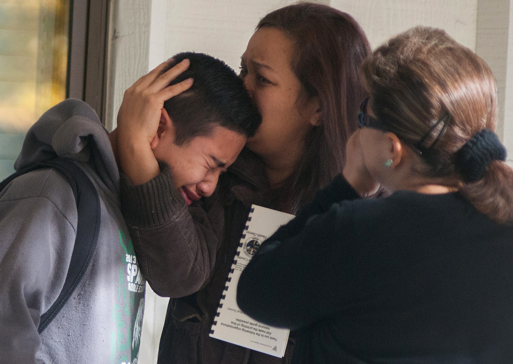 . A  Sparks Middle School student cries and is comforted after being released from Agnes Risley Elementary School, where some students were evacuated to after a shooting at SMS in Sparks, Nev. on Monday, October 21, 2013 in Sparks, Nev.  (AP Photo/Kevin Clifford)