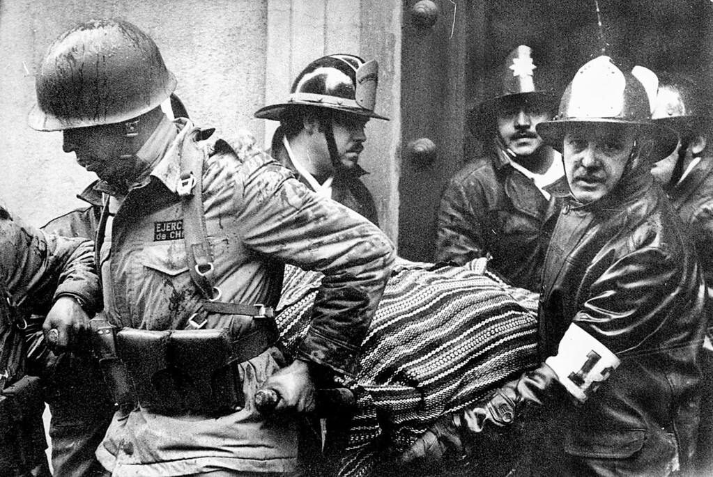 . In this Sept. 11, 1973 file photo, soldiers and firefighters carry the body of President Salvador Allende, wrapped in a Bolivian poncho, out of the destroyed La Moneda presidential palace. As bombs fell and rebelling troops closed in on the national palace in the coup led by Gen. Augusto Pinochet, Allende avoided surrender by shooting himself with an assault rifle, ending Chile\'s experiment in nonviolent revolution and beginning 17 years of dictatorship. (AP Photo/El Mercurio, File)