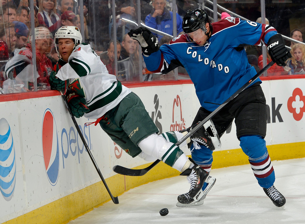 . Minnesota Wild right wing Jason Pominville, left, is slammed into the boards by Colorado Avalanche defenseman Erik Johnson (6) during the second period of an NHL hockey game on Saturday, Nov. 30, 2013, in Denver. (AP Photo/Jack Dempsey)