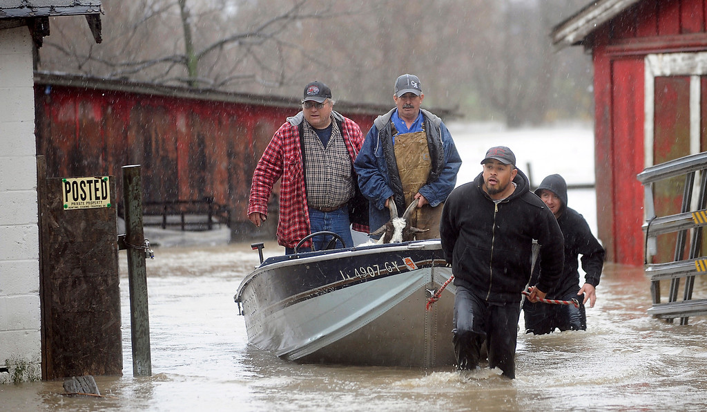 . Trino Sandoval pulls a boat with, from left, Steve McGwann, Jose Gonzalez and Rafael Quintana after they rescued a goat that was stranded in the flooded Hickory Creek near the farm Gonzalez rents in New Lenox, Ill., Thursday April 18,  2013.  (AP Photo/SouthtownStar, Matt Marton)