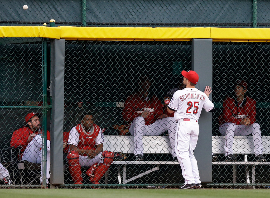 . Cincinnati Reds left fielder Skip Schumaker (25) watches a home run hit by Colorado Rockies\' Troy Tulowitzki clear the fence in the fourth inning of a baseball game on Friday, May 9, 2014, in Cincinnati. (AP Photo/Al Behrman)