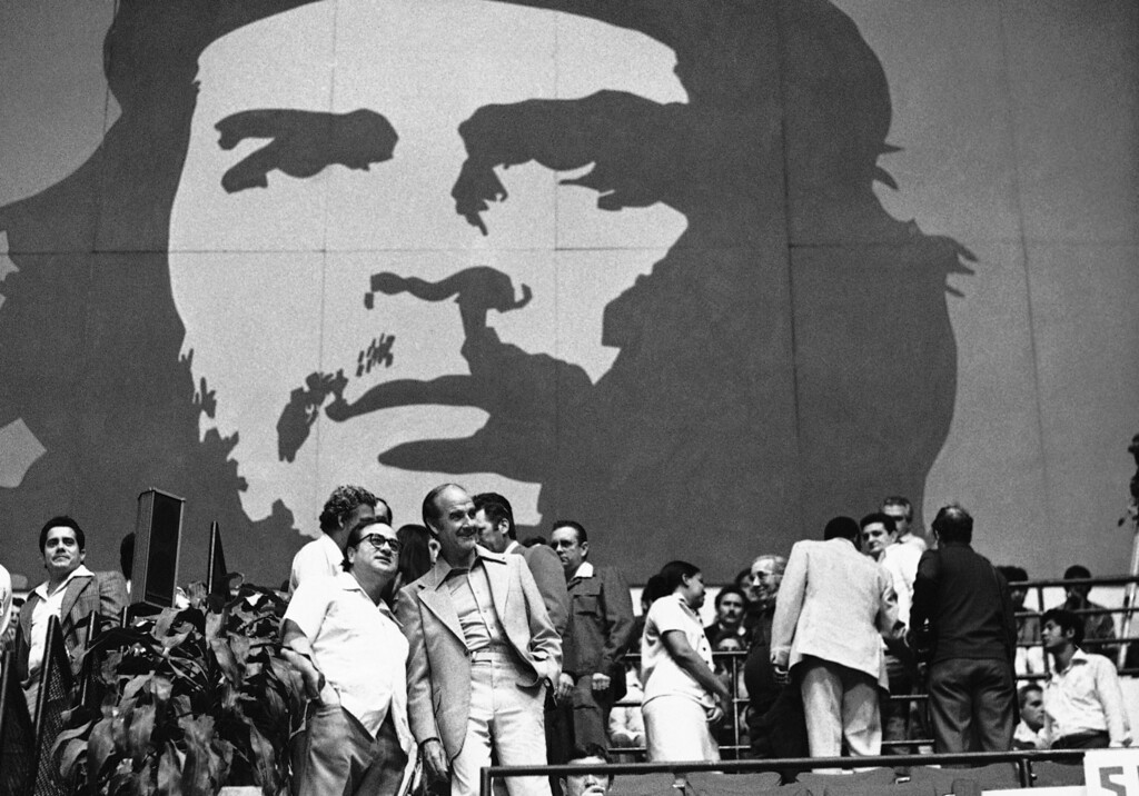 . Sen. James Abourezk, left, and Sen. George McGovern, both of South Dakota, prepare to take their seats in the Havana Coliseum, Wednesday, April 7, 1977 in Havana, Cuba, for the second basketball game between a team of South Dakota players and a Cuban all-star team. In the background is a large mural of Che Guevara. (AP Photo/Charles Tasnadi)