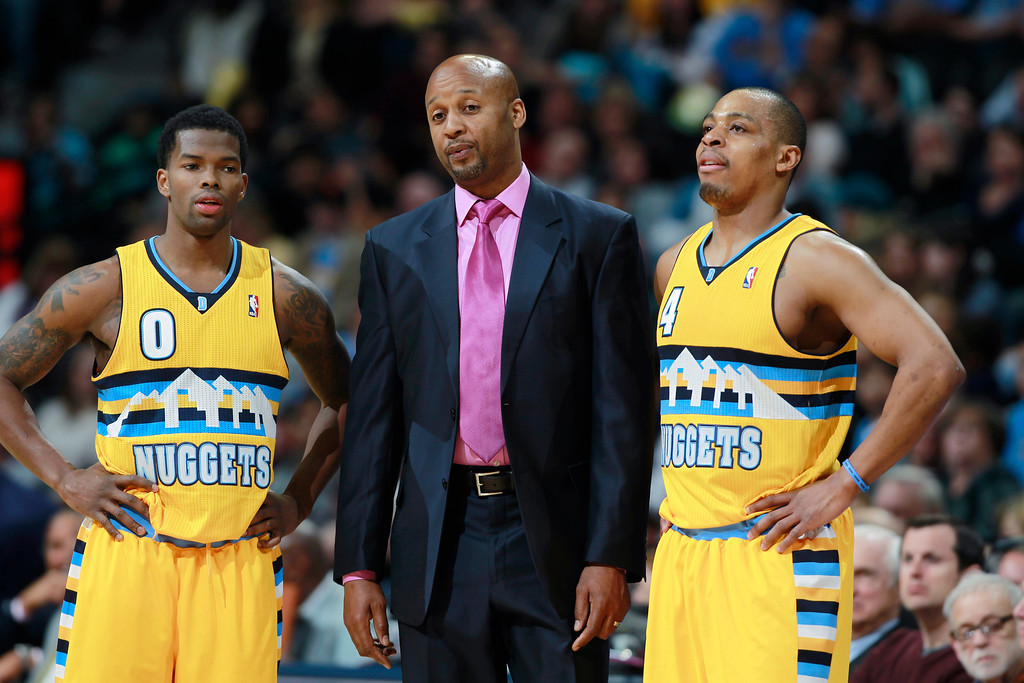 . Denver Nuggets head coach Brian Shaw, center, confers with guards Aaron Brooks, left, and Randy Foye during a time out against the Detroit Pistons in the fourth quarter of the Nuggets\' 118-109 victory in an NBA basketball game in Denver on Wednesday, March 19, 2014. (AP Photo/David Zalubowski)