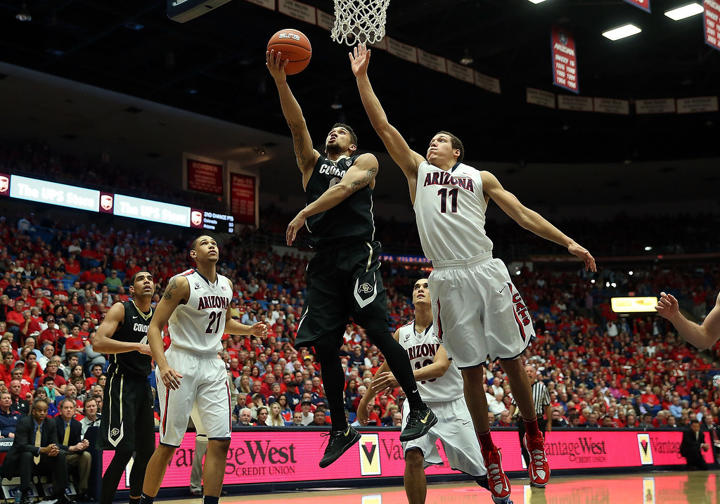 . Askia Booker #0 of the Colorado Buffaloes lays up a shot past Aaron Gordon #11 of the Arizona Wildcats during the second half of the college basketball game at McKale Center on January 23, 2014 in Tucson, Arizona. The Wildcats defeated the Buffaloes 69-57.  (Photo by Christian Petersen/Getty Images)