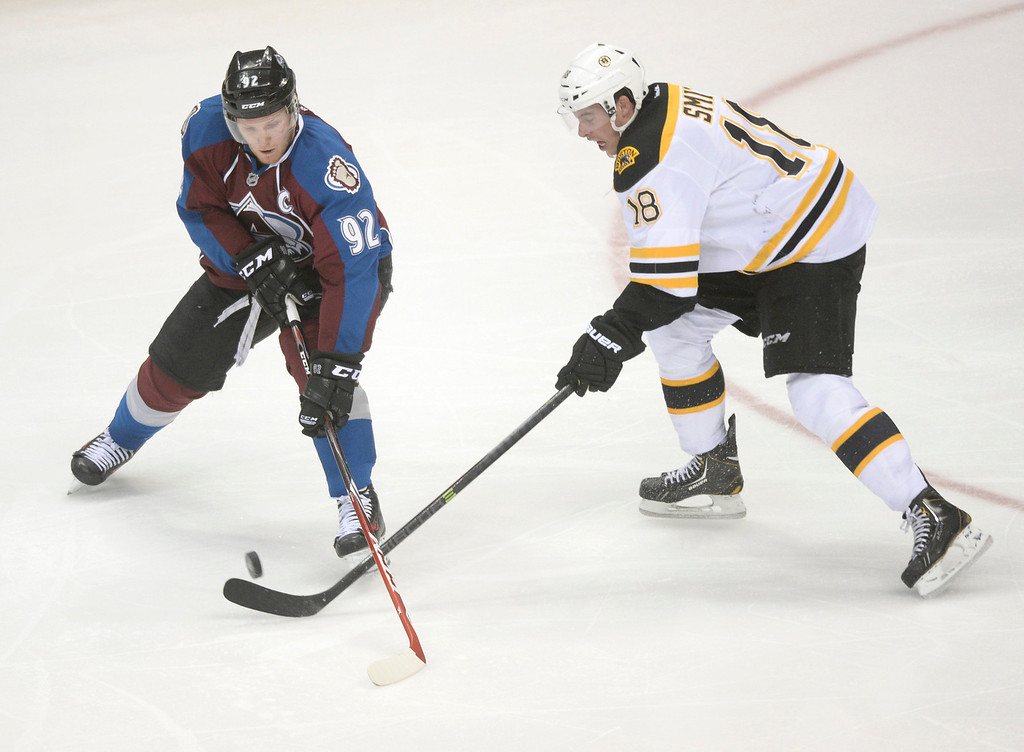 . Boston wing Reilly Smith (18) tried to stop Colorado center Gabriel Landeskog (92) in the second period. The Colorado Avalanche hosted the Boston Bruins at the Pepsi Center Friday night, March 21, 2014. (Photo by Karl Gehring/The Denver Post)