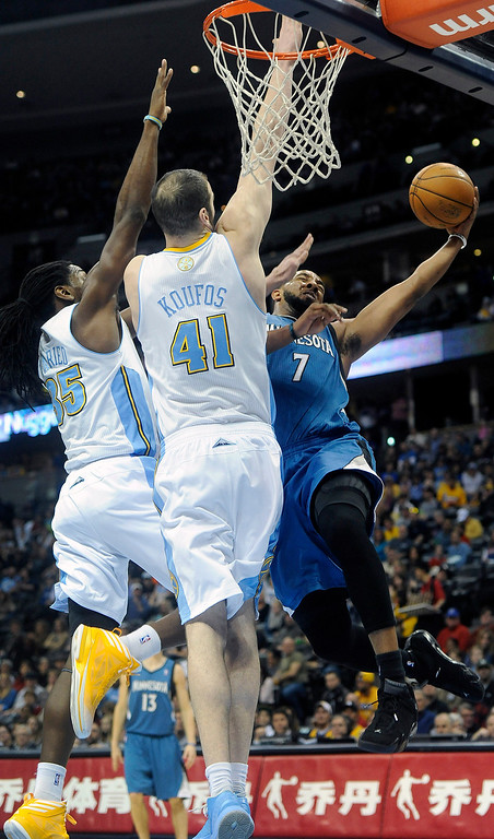 . Denver Nuggets forward Kenneth Faried, left, and center Kosta Koufos, center, defend the rim against Minnesota Timberwolves forward Derrick Williams, right, in the first quarter of an NBA basketball game on Saturday, March 9, 2013, in Denver. (AP Photo/Chris Schneider)