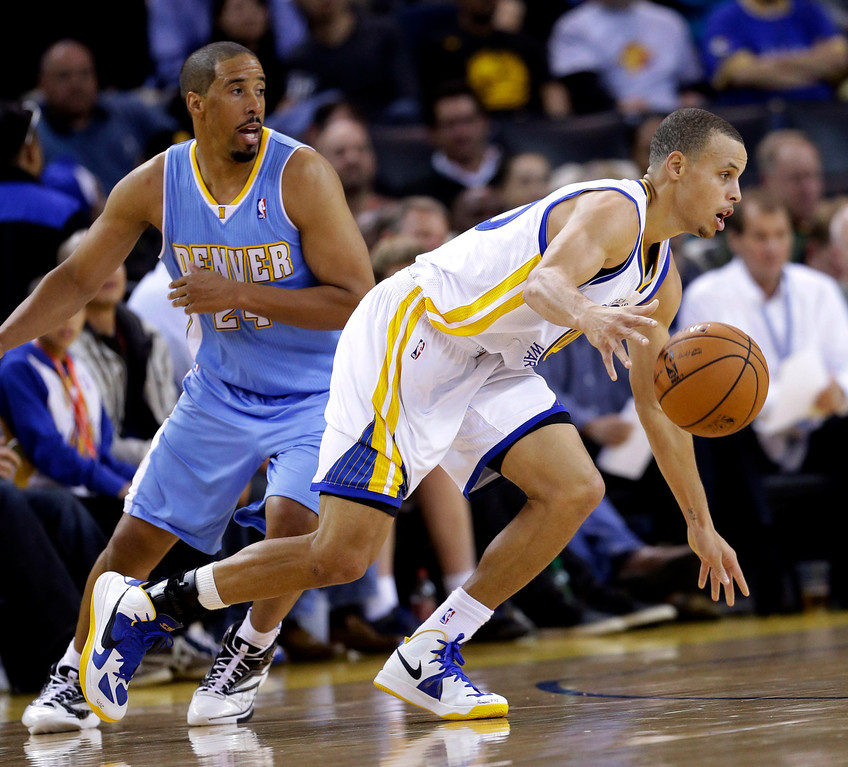 . Golden State Warriors\' Stephen Curry (30) dribbles past Denver Nuggets\' Andre Miller (24) during the first half of an NBA basketball game in Oakland, Calif., Thursday, Nov. 29, 2012. (AP Photo/Marcio Jose Sanchez)